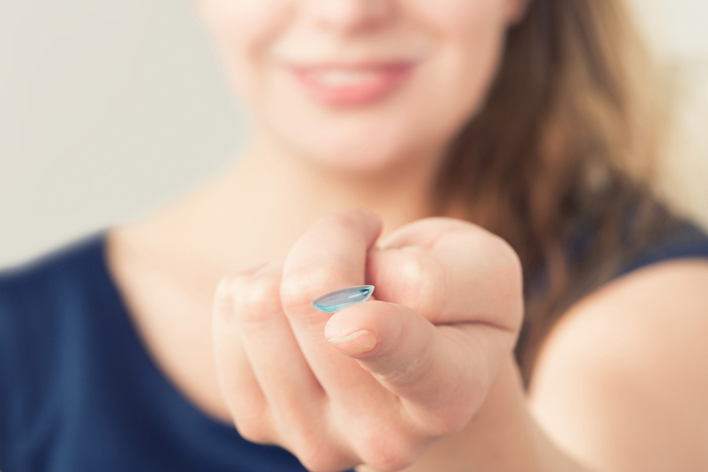 woman holding a contact lens on her finger